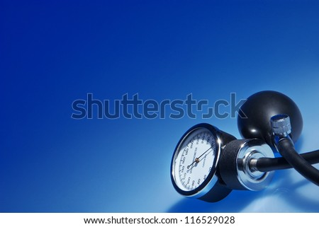 Sphygmomanometer on blue background - stock photo
