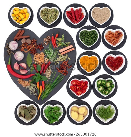 Spice and herb collection on heart shaped slate and rounds and in porcelain bowls over white background. - stock photo