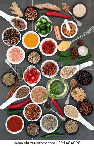 Spice and herb food seasoning sampler over grey slate tile background. - stock photo