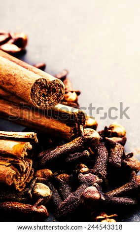 Spice background - various spices over dark table. Collection of different spices - cinnamon, black papper, anise star, peppercorns.  - stock photo