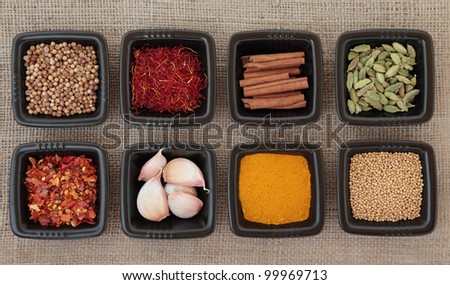 Spice collection of coriander and mustard seed, chili flakes, saffron,  cinnamon sticks, cardamom pods, turmeric, garlic cloves in black dishes on hessian sacking background.