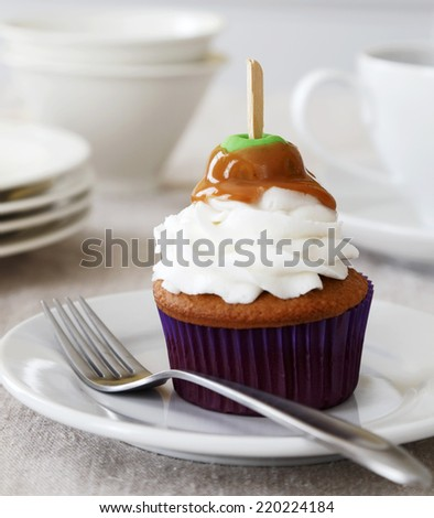 Spice cupcake with vanilla frosting decorated with a caramel apple