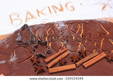 Spice for baking, anise and cinnamon sticks, cookie cutters on dough for Christmas cookies and gingerbread, concept of baking and Christmas time - stock photo