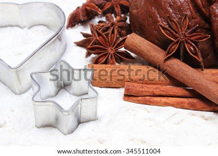 Spice for baking, cookie cutters, dough for gingerbread and Christmas cookies lying on white flour, concept of baking and christmas time - stock photo