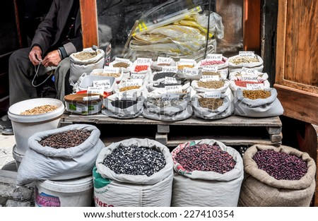 Spice market stall with heaped sacks and vendor in background - stock photo