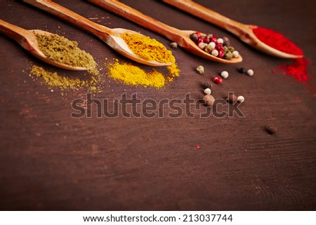 Spice on a wooden spoons over brown background - stock photo
