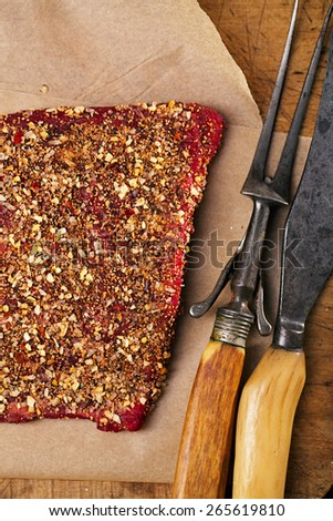 spice rubbed raw  beef, making jerky meat on woodeb backdrop with vintage curving fork and knife - stock photo