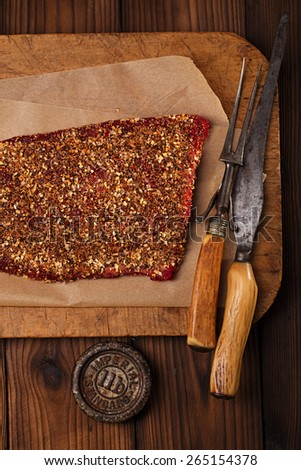 spice rubbed raw  beef, making jerky meat on wooden backdrop with vintage curving fork - stock photo