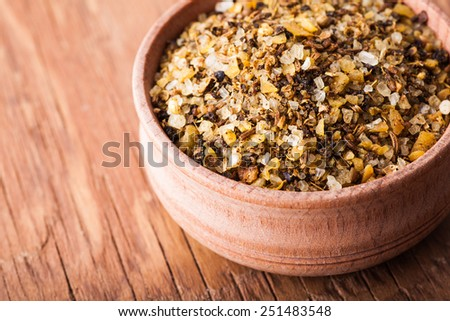 spice salt in a wooden bowl close-up on a vintage background - stock photo