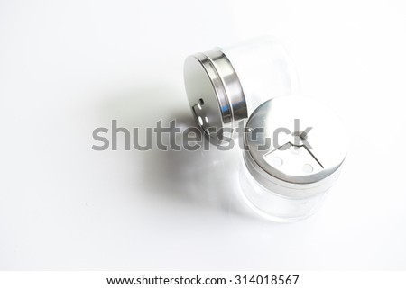 Spice shaker or salt shaker with a perforated metal lid. Isolated on white background. Slightly de-focused and close-up shot. Copy space.