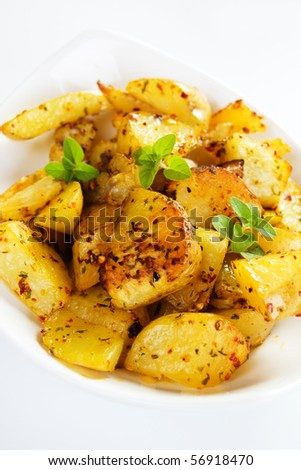 Spiced and tasty roasted potato served in white plate - stock photo