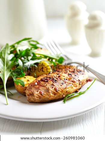 Spiced chicken breast with baked potatoes  and arugula - stock photo