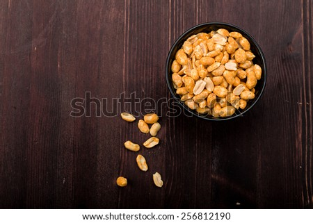 Spiced peanuts in a bowl on a Wooden underground - stock photo