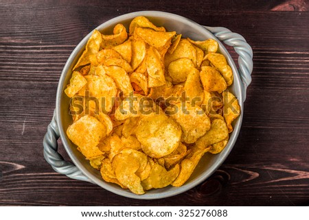 Spiced Potato chips in a bowl on a dark wooden background - stock photo