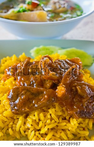 Spiced rice steamed with Turmeric (Curcuma longa) and cooked with meat. Serving with cow tail soup. This is a Thai Islamic dish in Thailand.