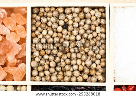 Spices and black rice in a wooden box: red, green and white pepper, sea salt, himalayan salt, allspice and coriander  - stock photo