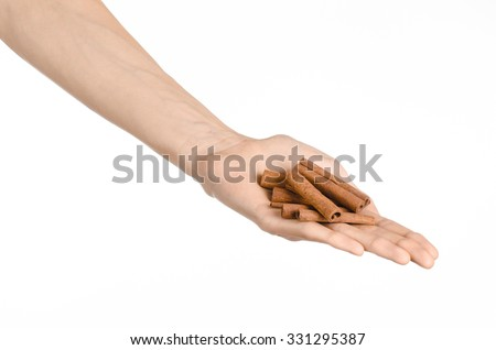 Spices and cooking theme: man's hand holding a brown pods cinnamon isolated on white background in studio