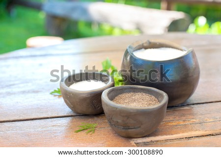 Spices and herbs in brown keramic bowls on wooden rural table. Sugar salt and black milled pepper. Vibrant summertime outdoors image. - stock photo