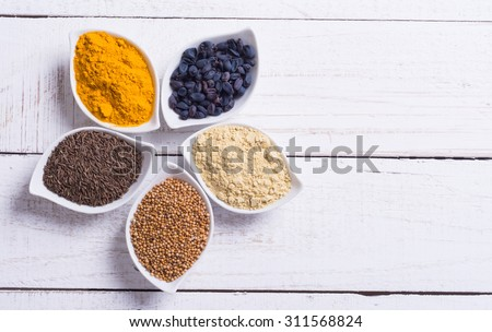 Spices and herbs in ceramic bowls on wooden background . Traditional Indian food . - stock photo