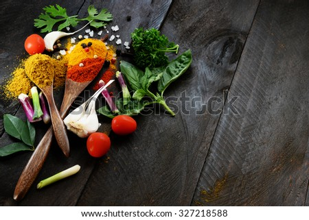 Spices and herbs in dark wooden table background. Indian spicy food concept. copy space for text. - stock photo