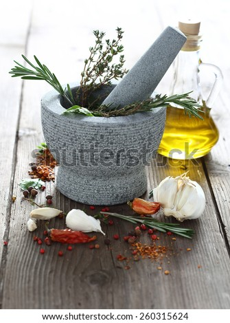 Spices and herbs in granite mortar shallow dof - stock photo