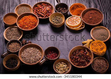 spices and herbs on black wooden table.