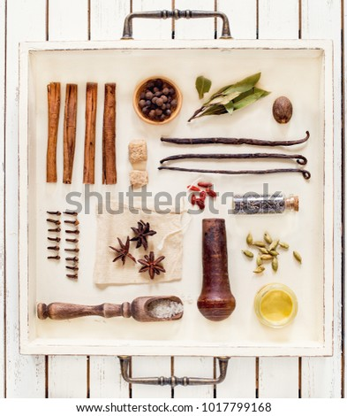 Spices and herbs on white rustic tray.