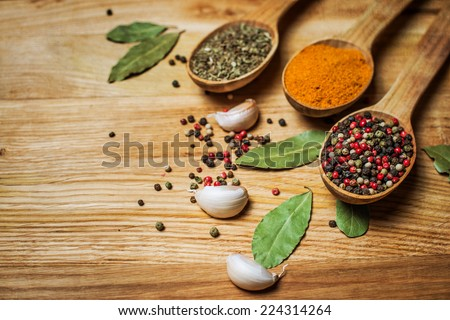 Spices and herbs. Spice greens in spoons on wooden background. Curry, turmeric, basil, pepper and other over wooden background. Retro styled. Textured. - stock photo