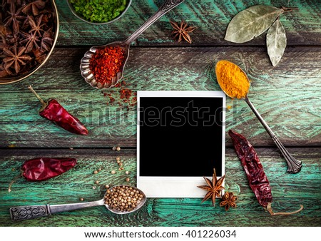Spices, blank photo frame and dry red chili peppers at wooden green background with spoons nearby - stock photo