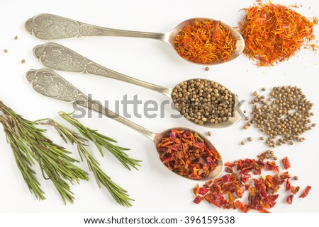 Spices: coriander, peas, saffron petals of red pepper on spoons. Sprigs of rosemary. White background - stock photo