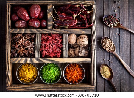 Spices, dry fruits and walnuts in the wooden box - stock photo