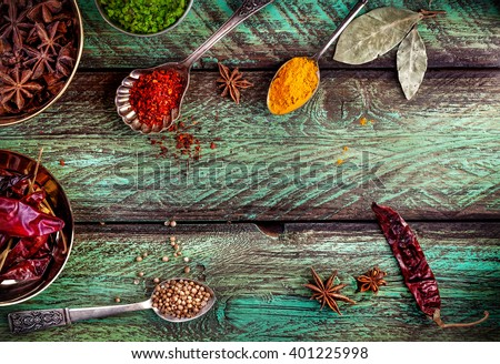 Spices, dry red chili peppers at wooden green background with spoons nearby - stock photo
