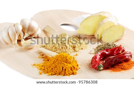 spices for curry on a wooden palette isolated on white