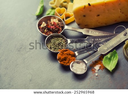 spices for Italian pasta in metal measuring spoons - stock photo