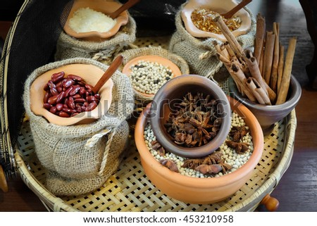 Spices herbs and seed beans in sacks and clay mortar, Local herbs in Thailand. - stock photo