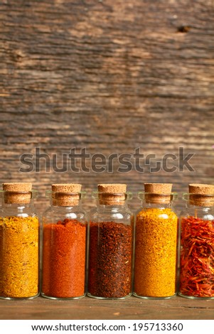 Spices, herbs and seeds for cooking in little jar in a row