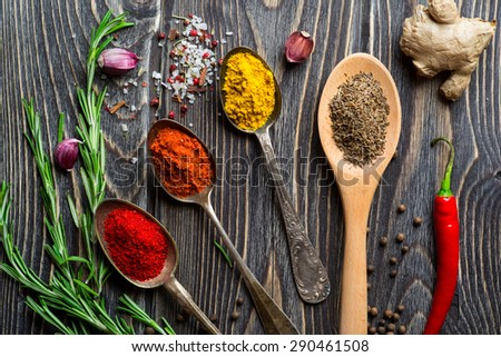 Spices. Herbs and spices selection in old metal spoons over wooden background. Rosemary, ginger and chili pepper. - stock photo