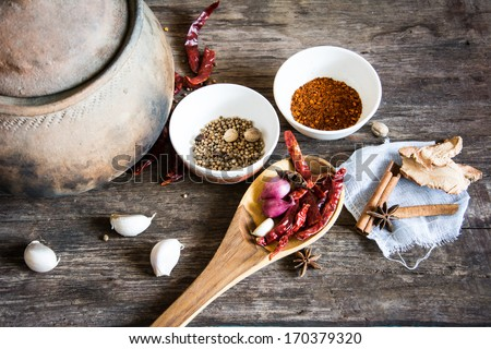Spices herbs in bowls and clay pot on old wooden table background . Food and cuisine ingredients. Colorful natural additives.  - stock photo