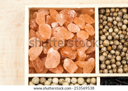 Spices in a wooden box: himalayan salt, coriander, white pepper and black rice - stock photo