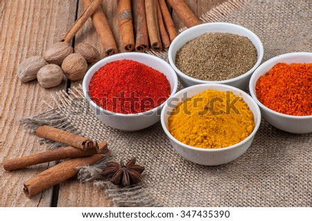 Spices in bowls on wooden background