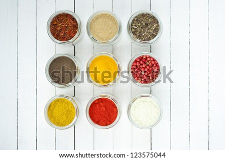 spices in glass jars on white wooden table, top view - stock photo