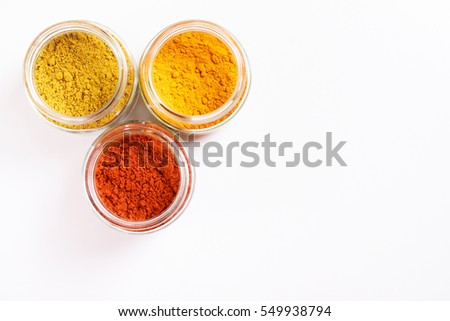 Spices in glass jars, turmeric, paprika, curry. Isolated on white. Empty space for text or inscription. Up view.