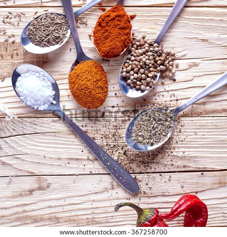 Spices in spoon. Salt and paprika, chilly powder, herbs and curry, saffron and turmeric and other on a wooden background - stock photo