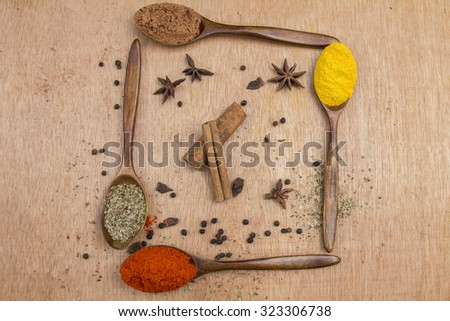 Spices in spoon with wood background