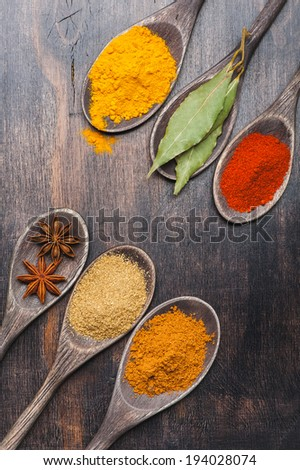 Spices in wooden spoons on dark background. Paprika, turmeric, masala, cinnamon, coriander, bay leaf