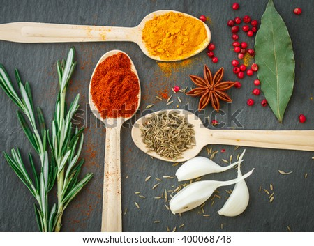 Spices in wooden spoons on the table - paprika, turmeric, cumin, star anise, garlic, rosemary, pepper, Bay leaf - stock photo