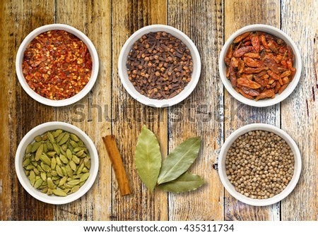 Spices including chilli flakes, cloves, bird's eye chillies, cardamoms, cinnamon stick, bay leaves and coriander seeds in white pots on a distressed wooden board