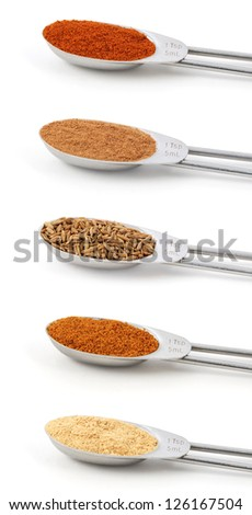 Spices measured in metal teaspoons, isolated on a white background: paprika, ground cinnamon, whole cumin seeds, ground mace and ground ginger. - stock photo