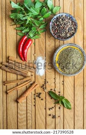 spices on cup, mint, cinnamon and pepper  on old wooden table background - stock photo