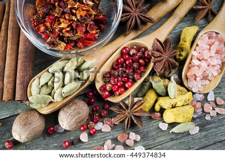 spices on wooden table, aniseed, himalayan salt, cinnamon, red pepper, cardamom, paprika, turmeric and nutmeg - stock photo